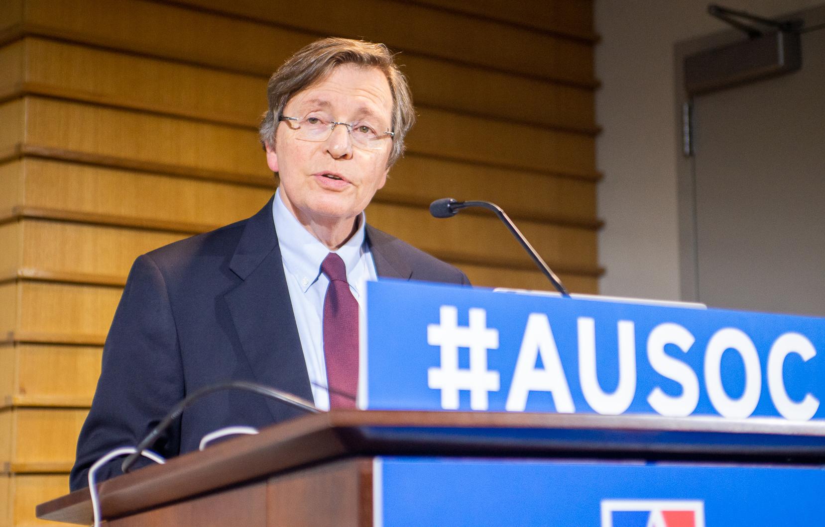 Charles Lewis speaking at podium