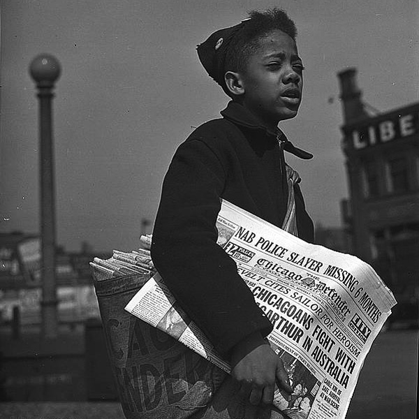 Newspaper boy selling the Chicago Defender in 1942