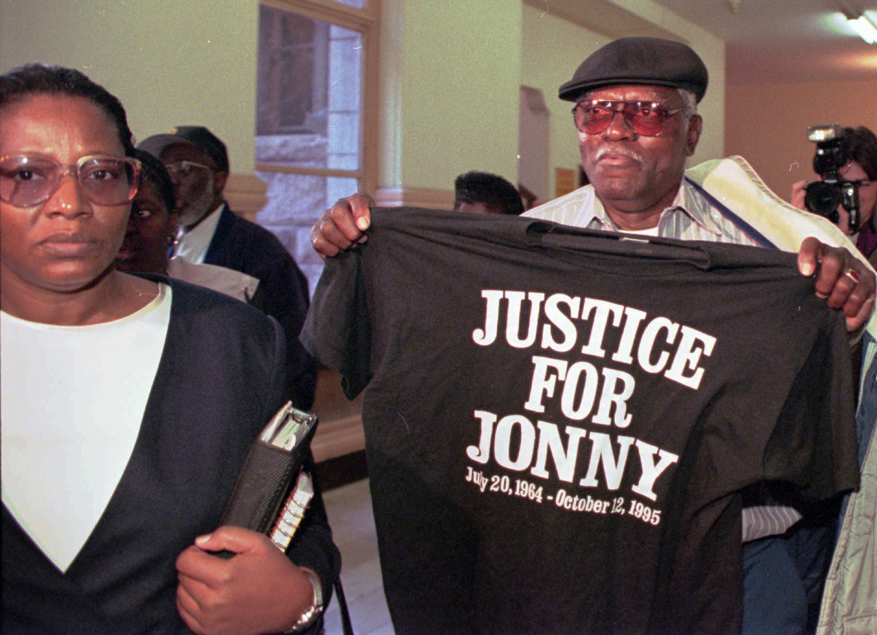 man holding up tshirt that reads 'Justice for Jonny'