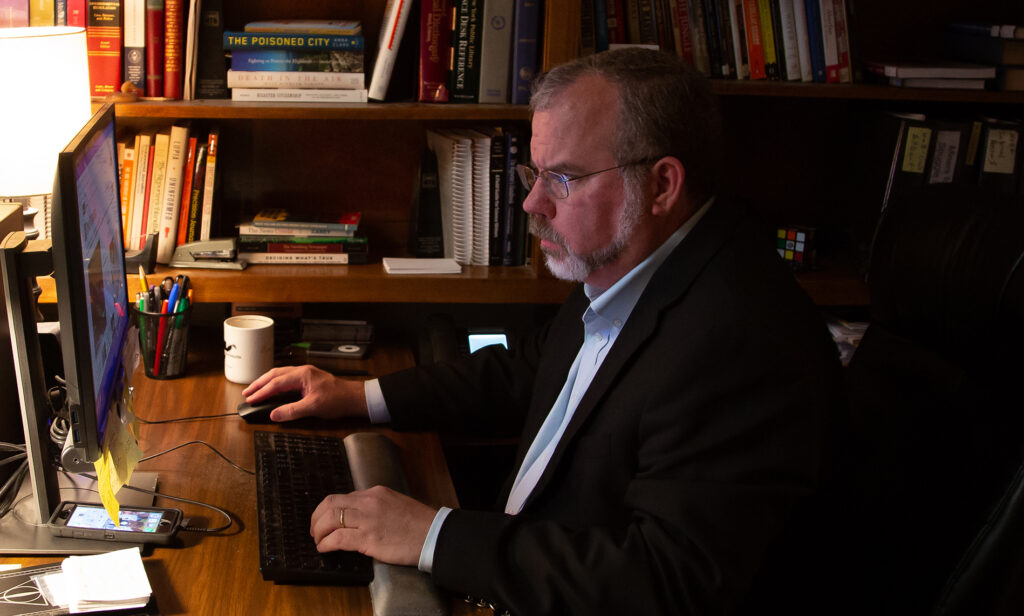 man sitting at desk working on computer
