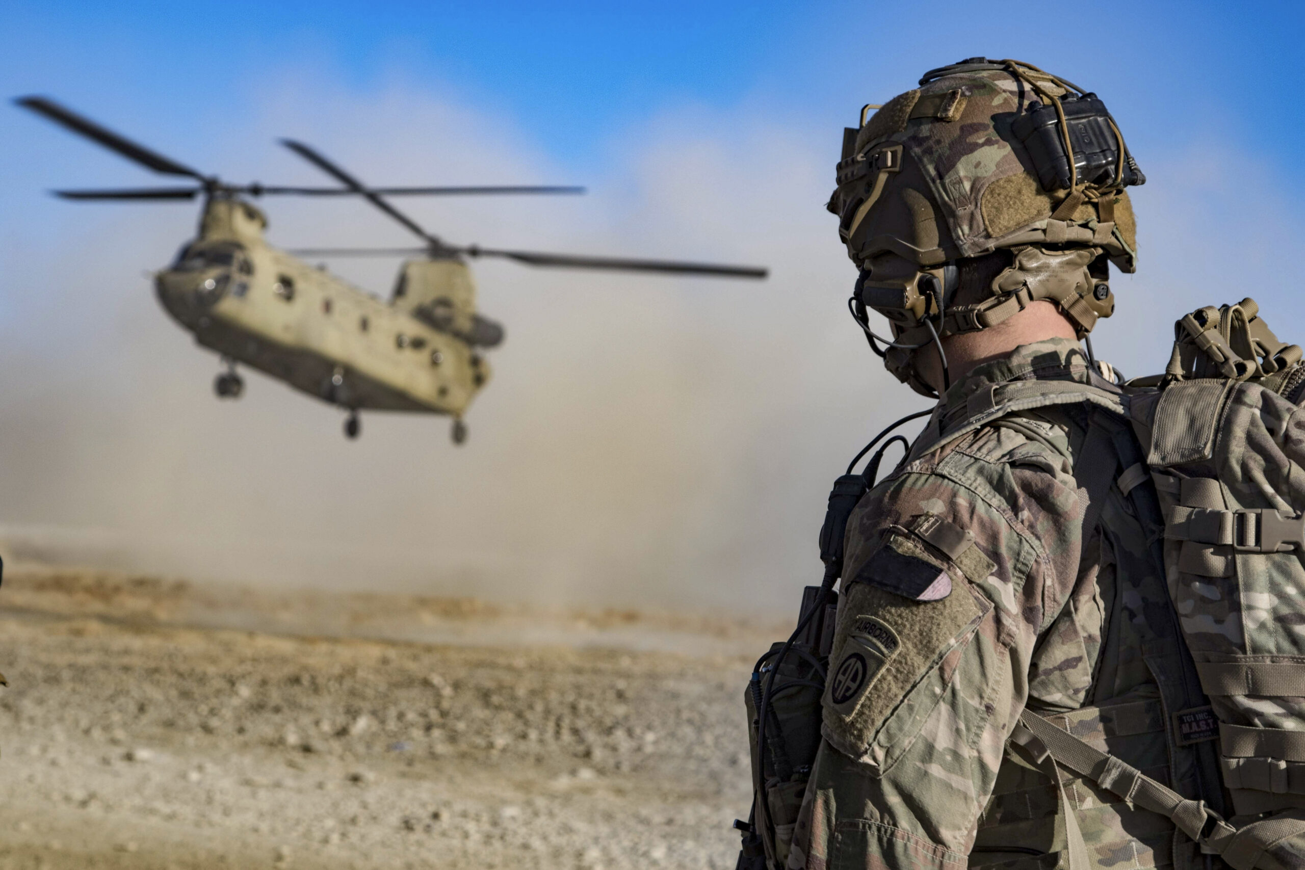 Army soldier watches helicopter land in Afganistan