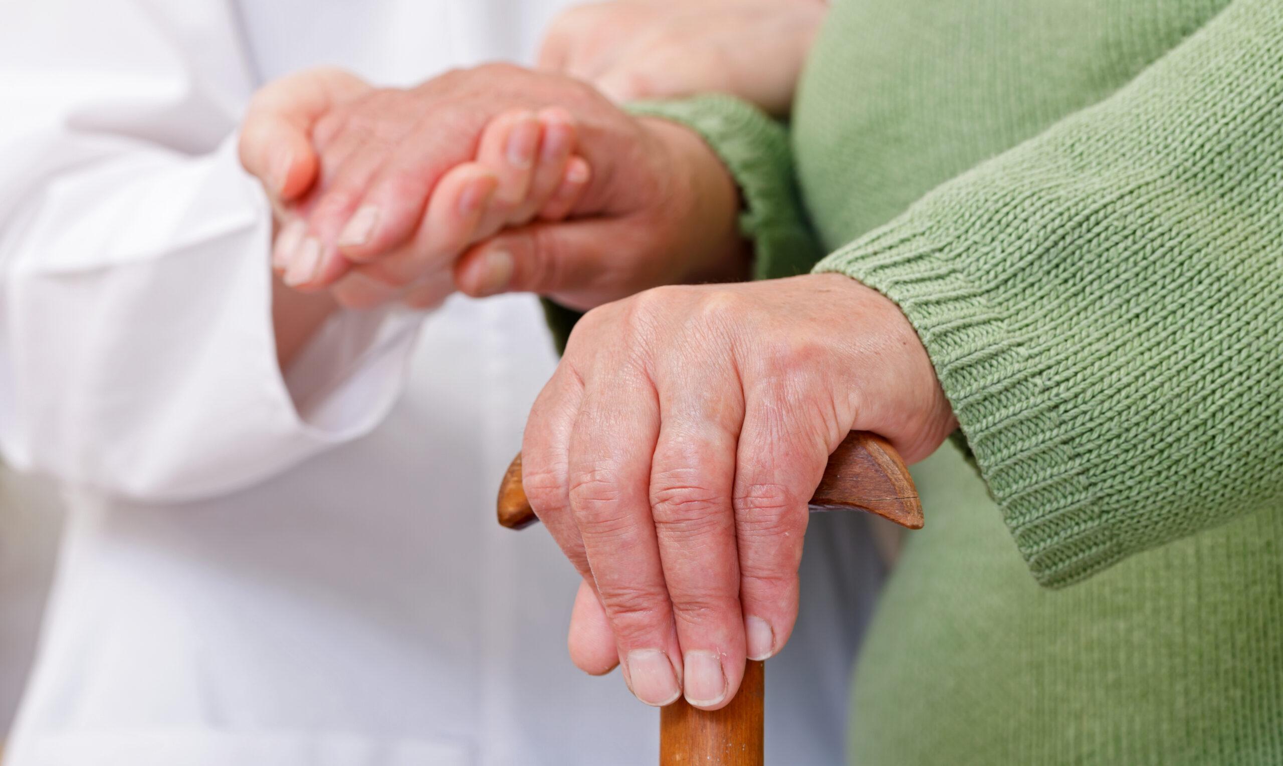 hands of nursing assistant and elderly resident