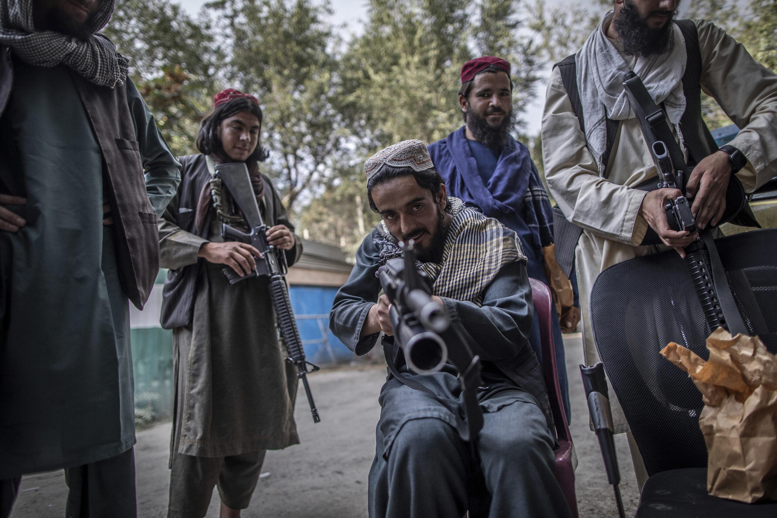 taliban fighter pointing gun at camera